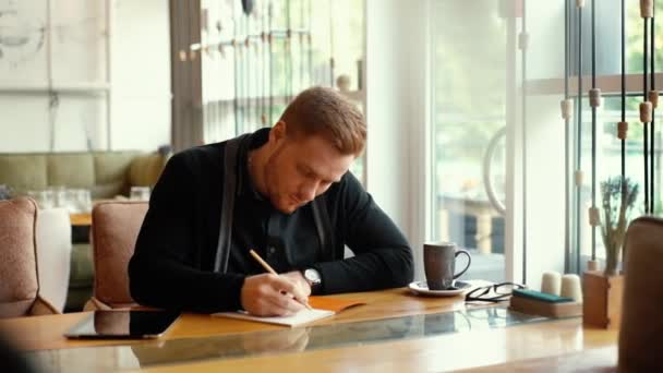 Young business man is working with documents, writing at table in cafe interior.