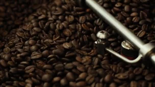 Close-up of mixing and stirred quality black coffee beans in roasting machine
