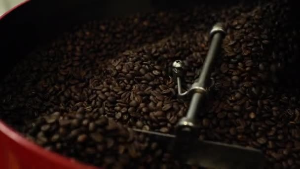 Close-up of mixing and stirred black coffee beans in roasting machine.