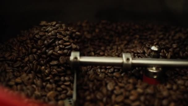 Close-up of mixing and stirred fragrant black coffee beans in roasting machine.