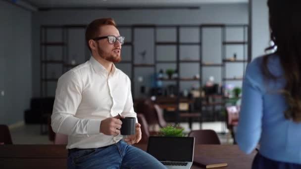 Mladý podnikatel drží šálek kávy a komunikuje se svým kolegou