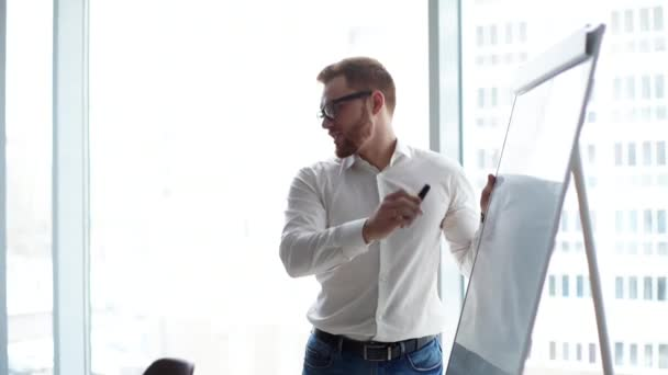 Young confident businessman presenting new project to partners on whiteboard