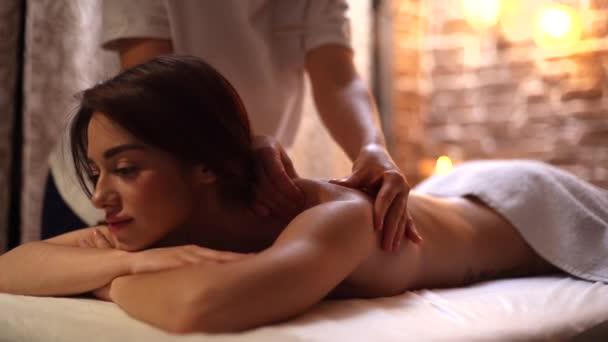 Portrét mladé ženy ležící na masážním stole, dostávající masáž ramen