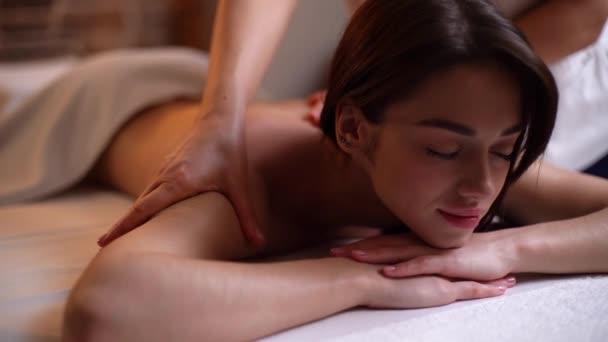 Relaxovaná žena ležící na lázeňské posteli se zavřenýma očima relaxuje při masáži zad
