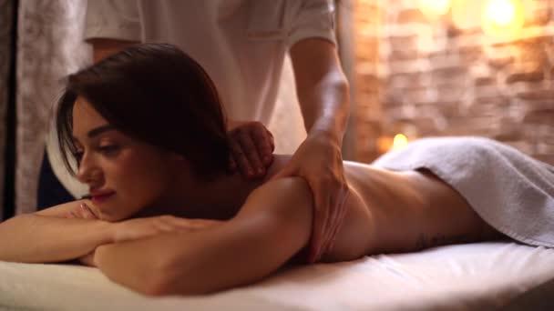 Žena masérka provádí masáž ramen a zad mladé ženě v lázeňském centru