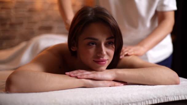 Detailní záběr krásné mladé ženy při masáži zad v lázeňském salonu