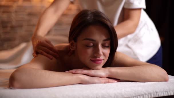 Krásná nahá dívka s perfektní pletí se zavřenýma očima relaxující během masáže