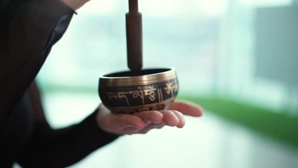 Közelkép női kéz játszik a kis tibeti Singing Bowl.