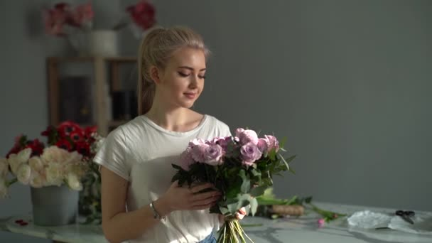 Smiling beautiful young woman wearing fashion clothes holding bouquet.