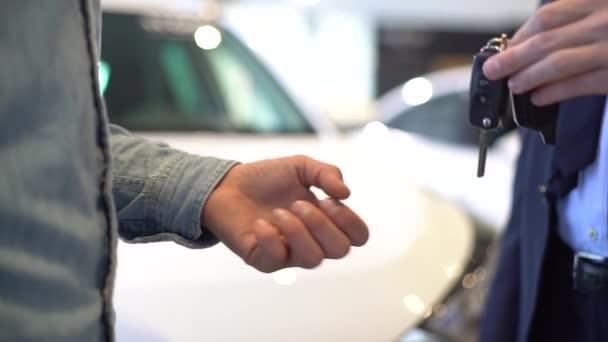 Detailní záběr prodejce dává klíčky od auta zákazníkovi a potřásá mu rukou.