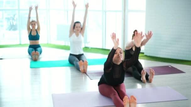 Skupina mladých flexibilních žen předvádí Paschimottanasana pózovat ve třídě jógy.