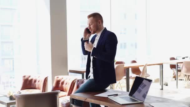 Komoly fiatal üzletember divatöltönyt visel, mobilon beszél..