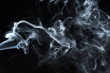 Background image of a wisp of smoke on a dark background. The texture of the flowing smoke. Frozen smoke on a dark background. Graphic resources dark backdrop. Texura of white clouds of fog. Curls of smoke frozen in motion.