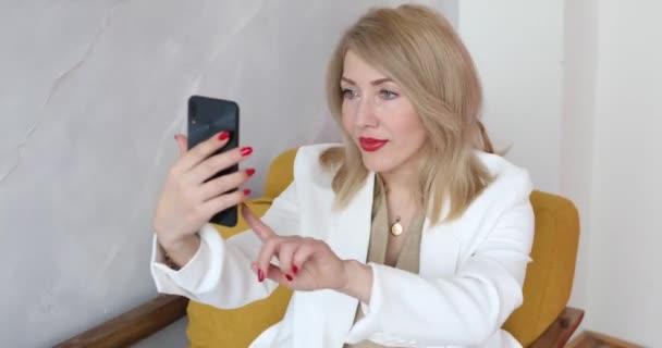 Blondine macht Fotos von sich am Telefon