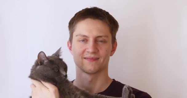 chlap na bílém pozadí hraje s šedou nadýchanou kočkou