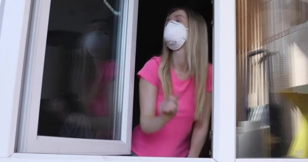 dívka v lékařské masce zavře okno