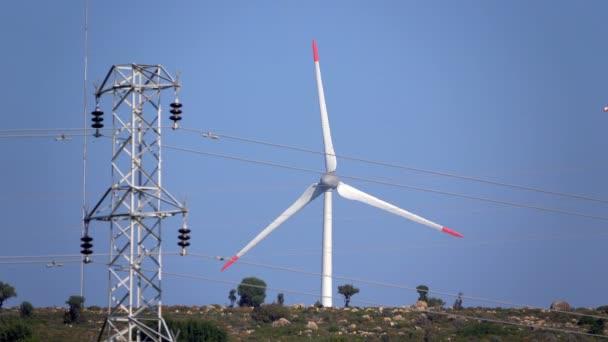 Větrné turbíny a starý kamenný maják.