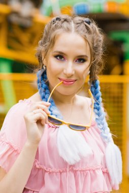 A beautiful girl with blue pigtails and bright pink and lilac pr
