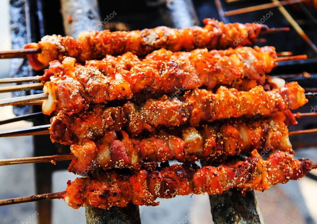skewers fried meat on a grill