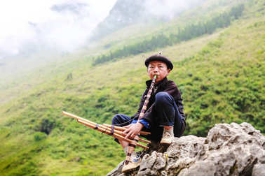 HA GIANG, VIETNAM, November 14th, 2017: Hmong young men playing a traditional instrument, northern Vietnam