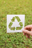 male hand holding cut paper with logo of recycling over green grass