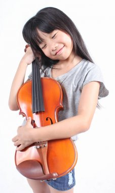 Little asian girl smiling and holding violin isolated on white background
