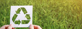 hands holding cut paper with logo of recycling over green grass background