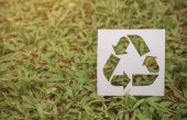 cut paper with logo of recycling over green grass