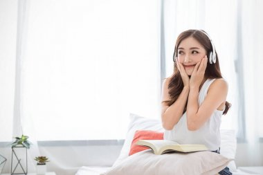 Portrait of young beautiful asian woman relax holding book listen to music from headphone in bedroom. Smile happy asian girl relaxing. Knowledge education university lifestyle, back to school concept