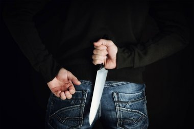 riminal with large sharp knife behind his back