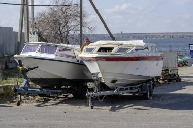 Two motor boats on trailers at parking. Used boats outdoors. Preparation for repair of water transport. Presale preparation or seasonal repair. Without people.