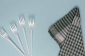 Fotografie Vier Plastikgabeln und ein Leinen-Küchentuch auf hellblauem Hintergrund. Weiße Einweggabeln und ein grün kariertes Handtuch. Servieren, Lebensmittelindustrie. Blick von oben. Nahaufnahme.