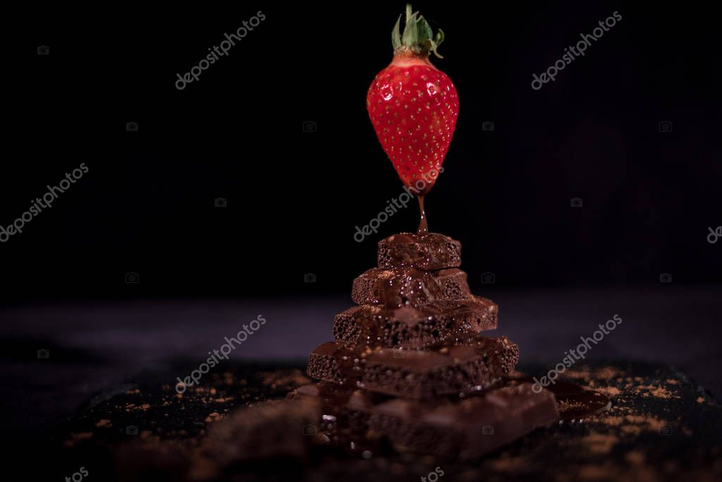One red straberry in the air on a top of dark chocolate