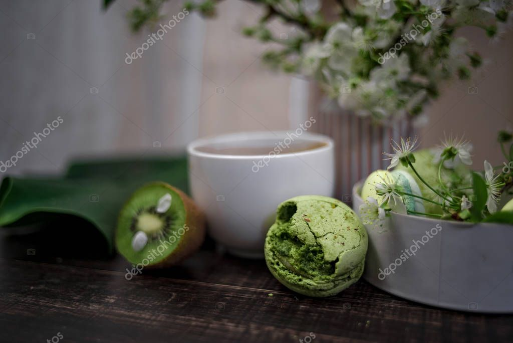 Green macarons on a wood table for coffee or a tea