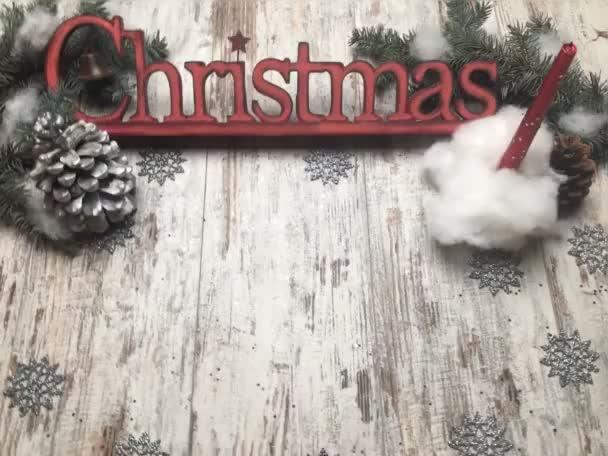 weihnachtsrote Logo-Buchstaben auf altem Holzhintergrund mit roter Kerze im Schneeball