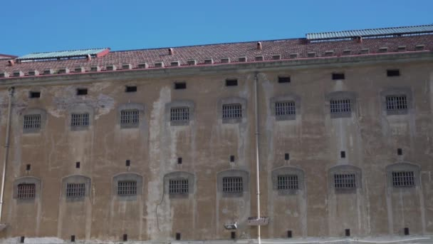 prison building wall with bars on the windows.