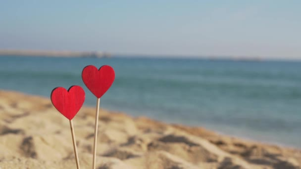 dvě červená srdce v písku na pozadí mořských vln s kopírovacím prostorem.