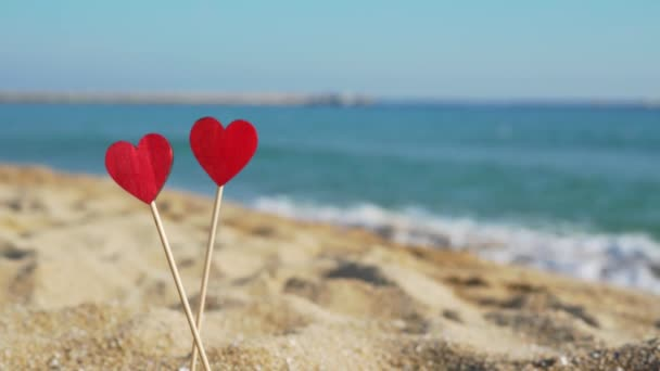 Zwei schöne Holzherzen auf dem Hintergrund des Meeres im Sand