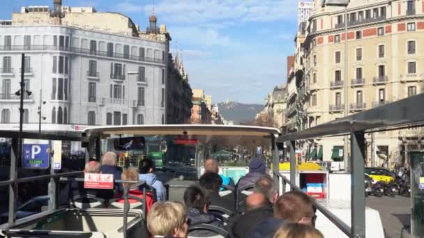 people ride a tourist bus on the street of Barcelona in winter in sunny weather