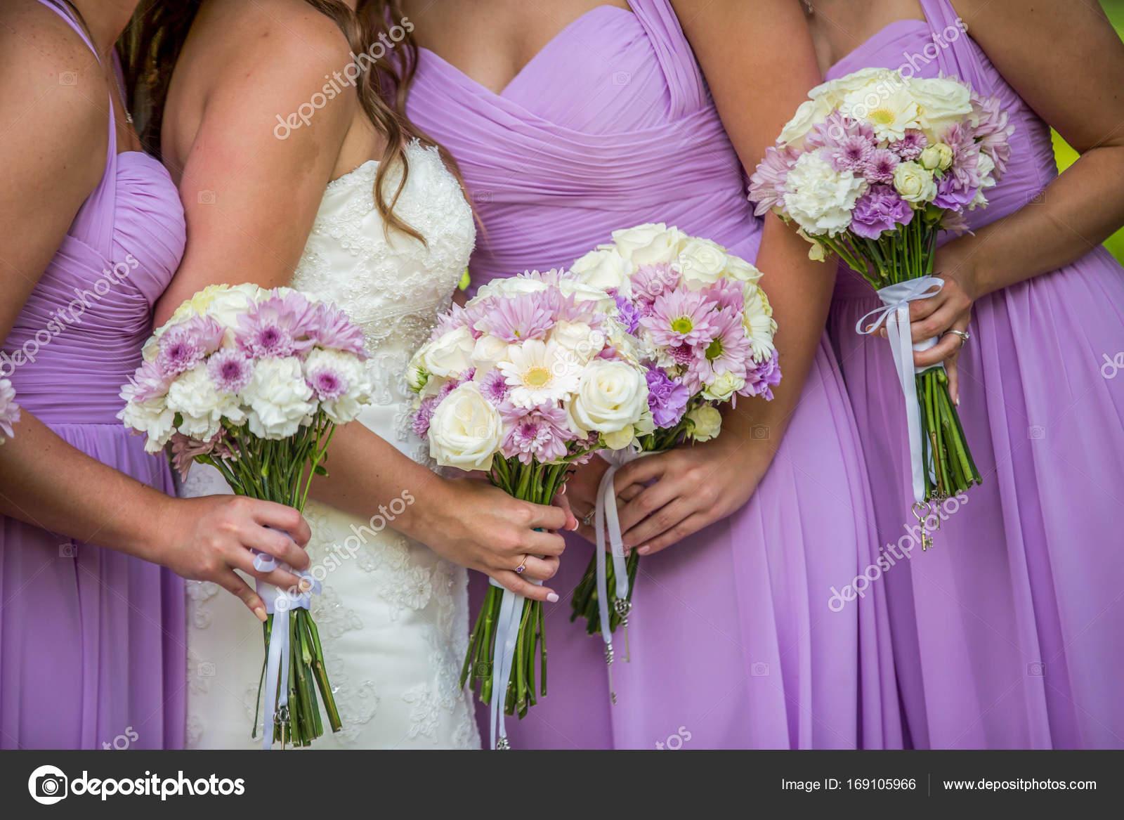 Novia y damas de honor vestidos púrpura sosteniendo sus ramos — Foto ...