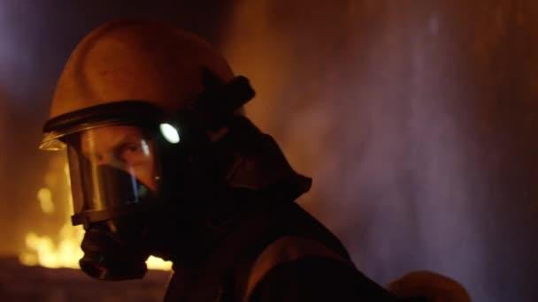 Budova je v plamenech. Statečný hasič otočí a hledí do kamery. Jazyky plamenů se olizovat zdi domu