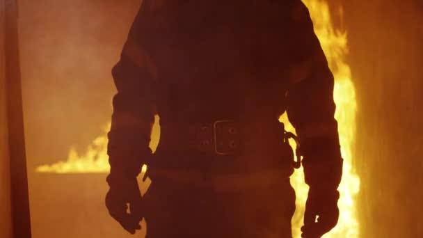 Portrét Shot statečný hasič stojící v budově hořící oheň, zuřící za ním. Otevřený oheň a kouř v pozadí
