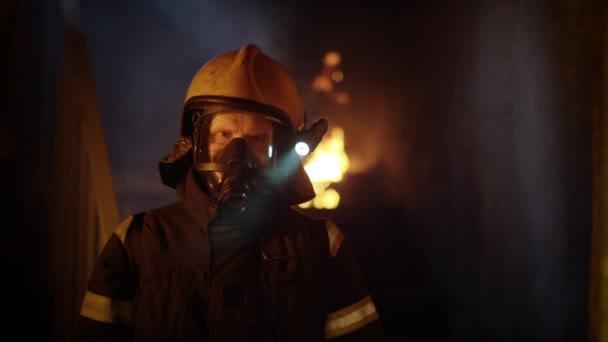 Portrét statečného hasiče stojící v hořící budově. Běsnící oheň vzplane v pozadí