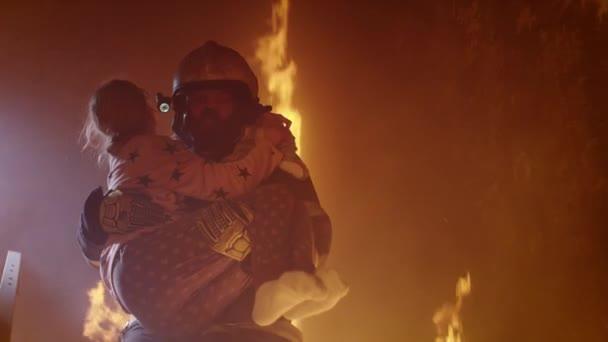 Statečný hasič sestupuje po schodech z hořící budovy s uloženou dívku v náručí.