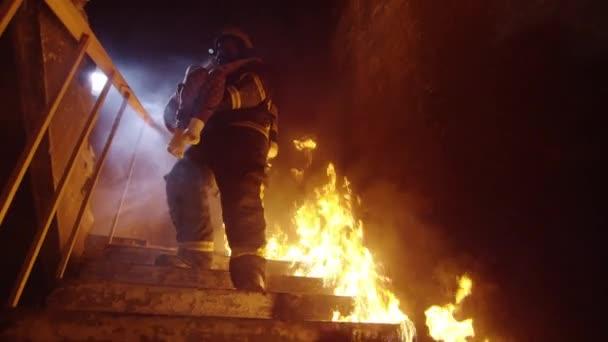 Statečný hasič sestupuje, hořící schodiště s uloženou holčička ve svých rukou. Otevřeným ohněm jsou vidět všude.