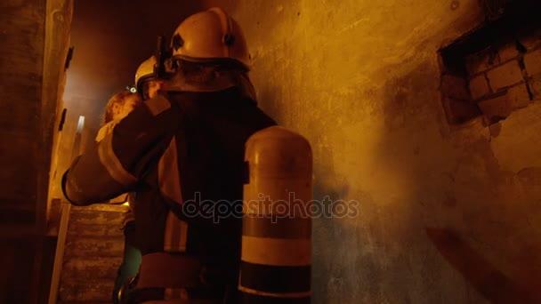 Budova je v plamenech. Statečný hasič průchody na uložené dívka na jeho spoluhráč. Kdo ji přivádí do bezpečí