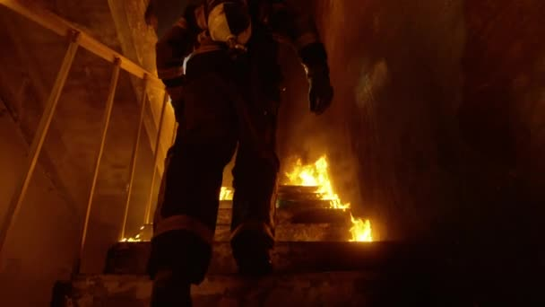 Statečný hasič běží po schodech hořící. Oheň je všude. V pomalém pohybu.