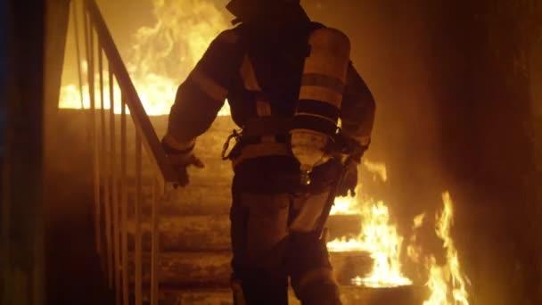 Statečný hasič běží nahoru po schodech. V pomalém pohybu. Běsnící oheň je vidět všude