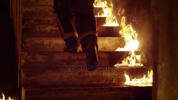 Detail hasičská nohy běží po schodech pálení. Budova je v plamenech otevřené plameny jsou vidět všude. Zpomalený pohyb