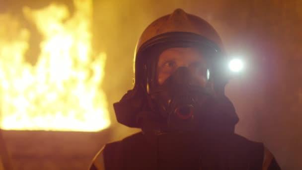 Portrét Shot statečný hasič stojící v budově hořící oheň, zuřící za ním. Otevřený oheň a kouř v pozadí.